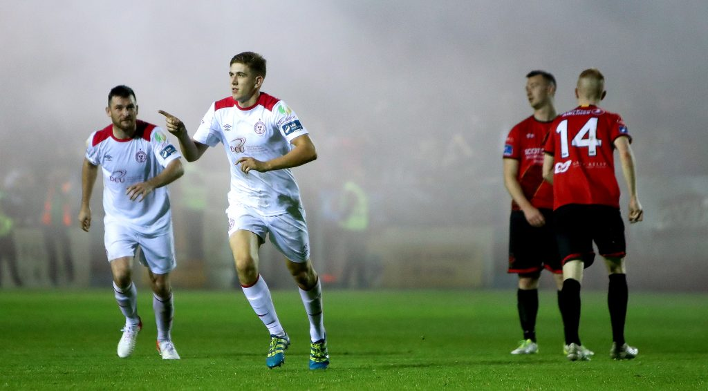 Two Shelbourne FC players on pitch wearing white away jerseys at an SSE Airtricity League match against Drogheda United