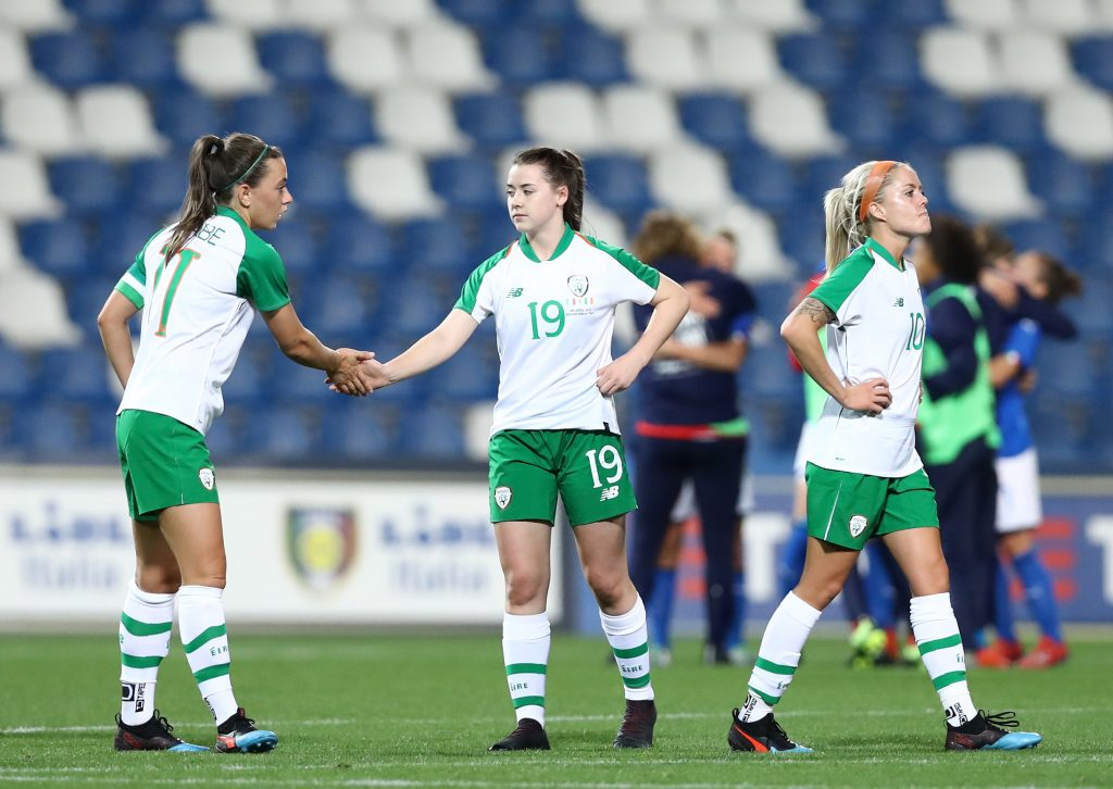 Three players from Shelbourne FC's Womens team on pitch wearing Republic of Ireland jerseys.
