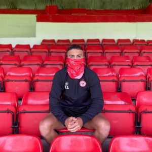 Shels player sits in the stands wearing Shels neck scarf